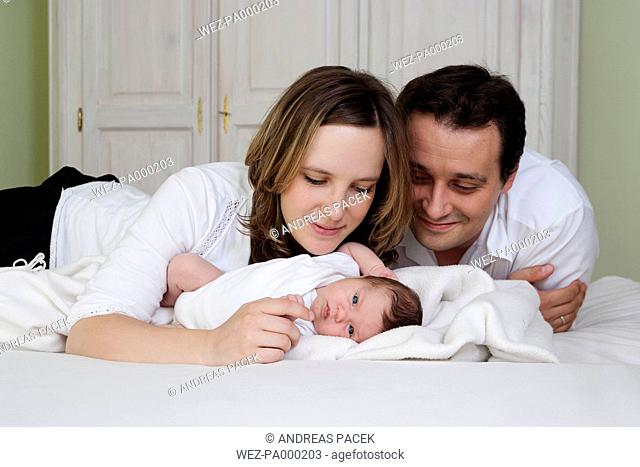 Parents with newborn baby girl lying on bed