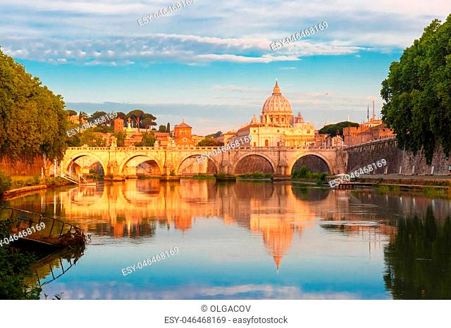 Saint Angel bridge and Saint Peter Cathedral with a mirror reflection in the Tiber River in the sunny morning in Rome, Italy
