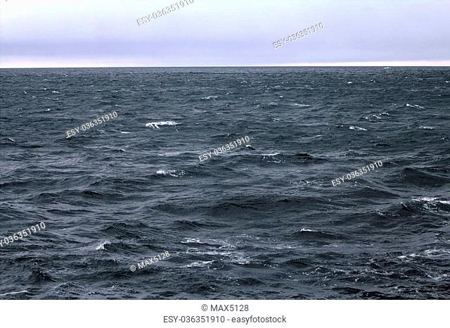High sharp waves in the Arctic sea. On the horizon of the Northern island of Novaya Zemlya