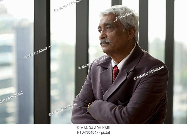 India, Portrait of senior businessman with arms folded looking through window