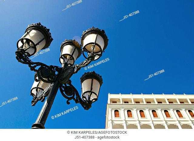 Puerto Rico, San Juan. Street lamp along Paseo de la Princesa, low angle view, part of older building