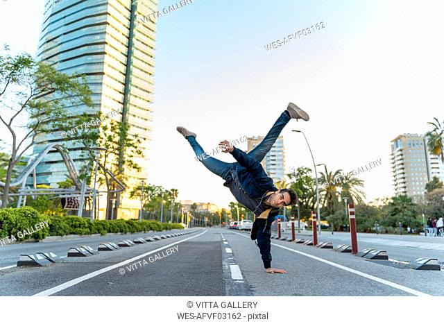 Man making a handstand on the street in the city, Barcelona, Spain