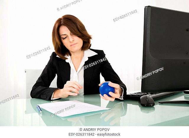 Photo Of Young Businesswoman Pressing Stressball In Office
