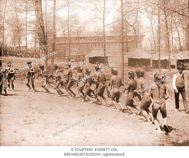 Igorot men from the Philippines dance in a semi-circle. The huts in the background are part of the Louisiana Purchase Exposition. 1904