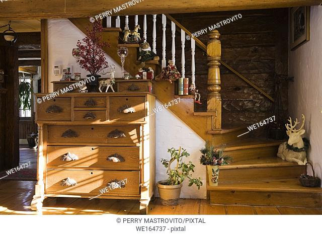 Dresser and staircase inside the living room of an Old Canadiana cottage style residential (1974 reconstructed) log home, Quebec, Canada