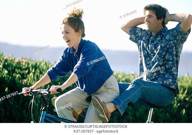 Couple having fun on tandem cycle on vacation