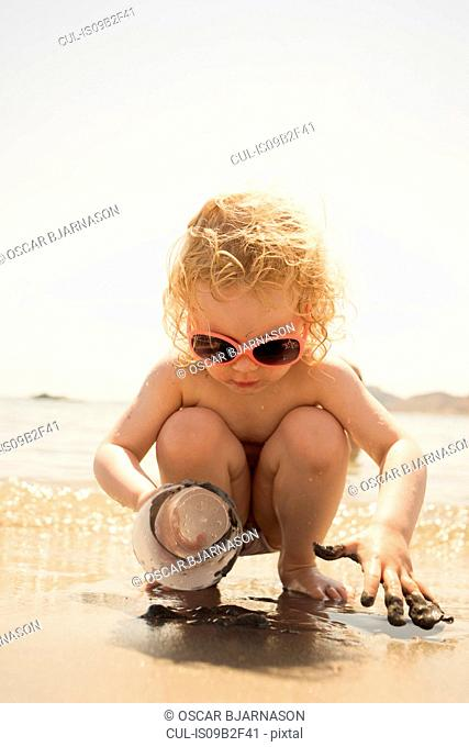 Cute girl crouching on beach playing with plastic cup in sand, Alicante, Spain