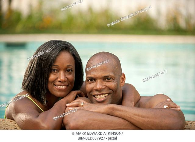 African American couple leaning on edge of swimming pool