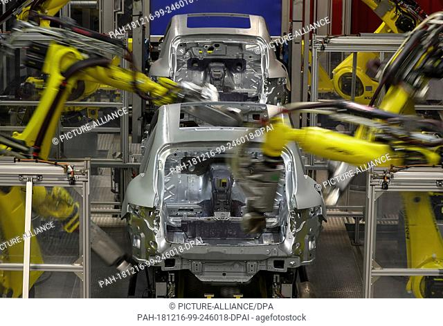 13 December 2018, Saxony, Leipzig: Several welding robots are working on a body of a Porsche Macan in the body shop in Leipzig