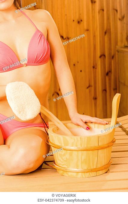 Closeup of woman in wood finnish spa sauna with exfoliating glove and ladle. Girl in bikini relaxing. Skin care concept