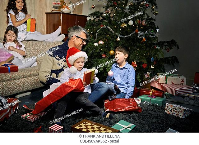 Father on sitting room floor opening christmas gifts with children