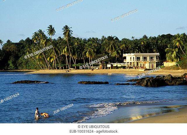 People standing in sea beside sandy beach with white painted building surrounded by palm trees