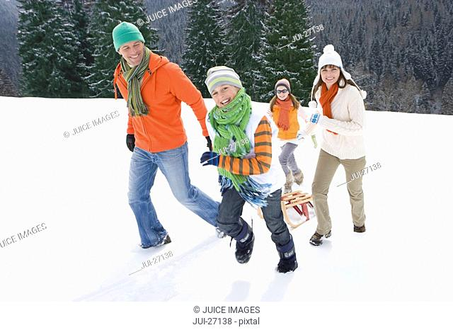 Family pulling sled up mountain top ski slope