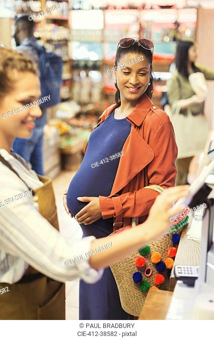 Cashier helping pregnant female shopper at grocery store cash register
