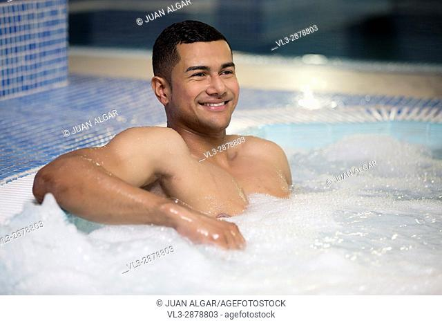 Horizontal indoors shot of smiling man looking away and having rest and relax in air bubble pool