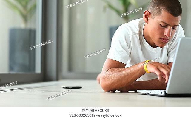 A young man using his laptop at home and then checking his cellphone - Copyspace