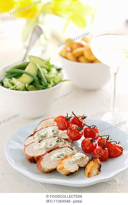 Stuffed chicken breast with roasted cherry tomatoes, vegetable salad and potatoes