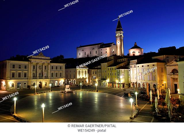 Empty Tartini Square in Piran Slovenia with City Hall, Tartini statue, St. George's Parish Church with baptistry, and St Peter's church at dawn