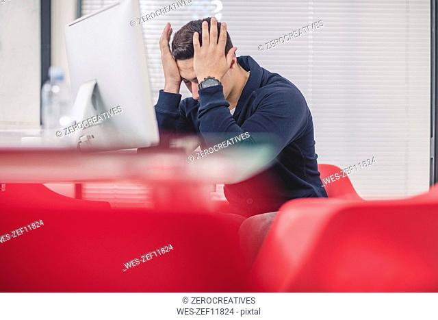 Businessman with head in his hands at desk