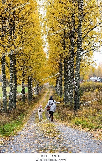 Finland, Kuopio, back view of mother and little daughter running side by side in autumn