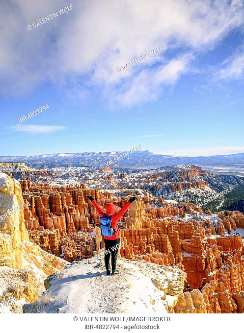 Young woman with outstretched arms overlooking the amphitheatre, bizarre snowy rocky landscape with Hoodoos in winter, Rim Trail, Bryce Canyon National Park