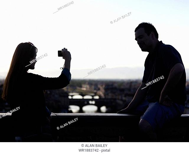 Italy, Florence, Couple on bridge over River Arno