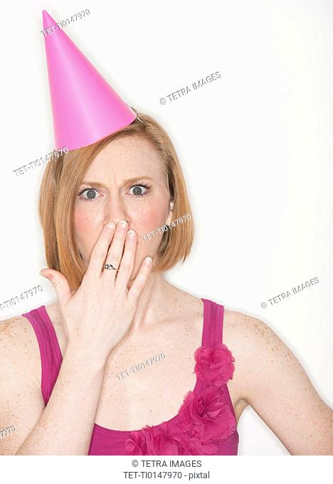 Woman wearing pink party hat covering lips with hand