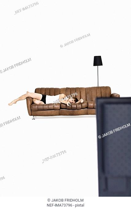 Young man lying in a couch watching TV