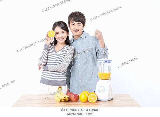 Young smiling newlyweds making juice