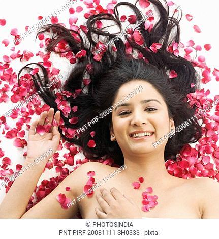 Woman lying on rose petals