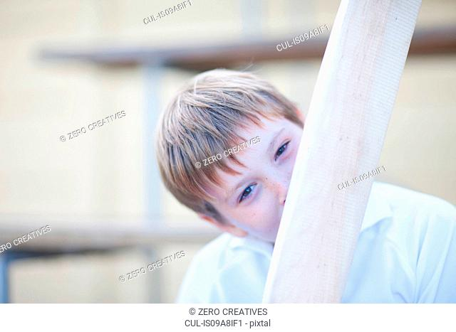 Boy holding cricket bat in front of face