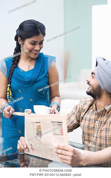 Man reading a newspaper while his wife serving tea