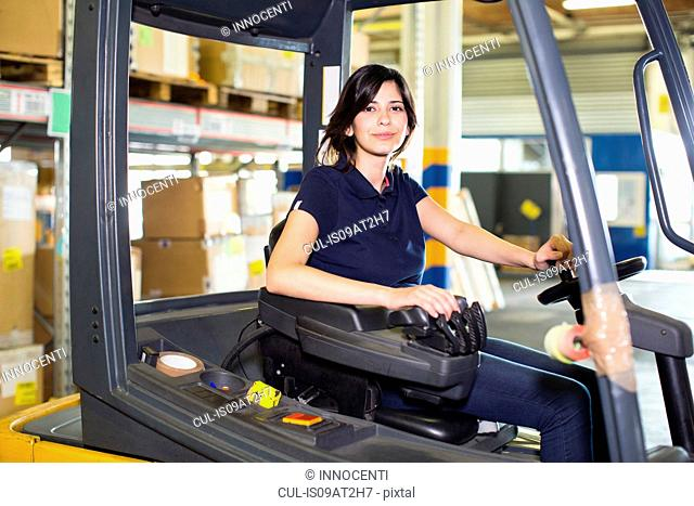 Portrait of female forklift truck driver working in distribution warehouse