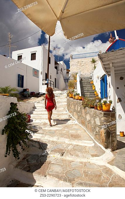 Woman walking in the alley of the Faros village, Sifnos, Cyclades Islands, Greek Islands, Greece, Europe