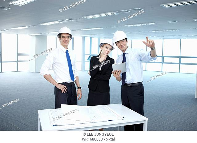 two men and a woman looking at building plans