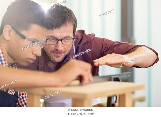 Carpentry teacher and student examining measurement