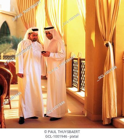 Arab men looking a palmtop