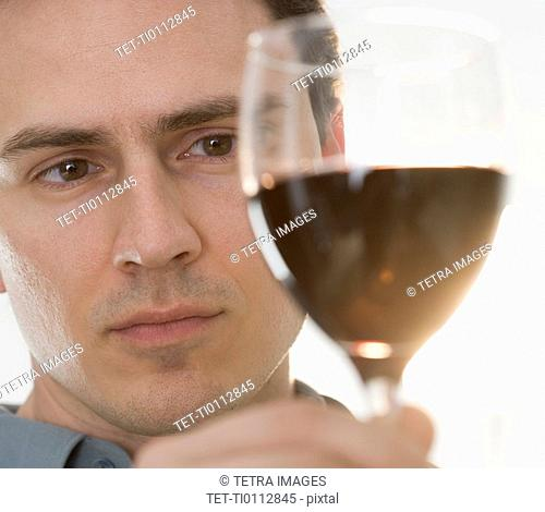 Man inspecting glass of red wine