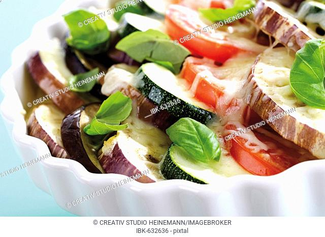 Vegetable casserole with tomatoes, eggplants, zucchini, cheese and basil
