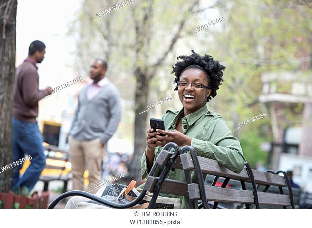 A woman on a bench checking her phone. Two men in the background