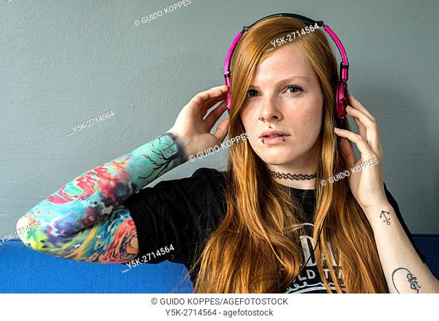 Tilburg, Netherlands. Young red haired woman listening to her music, uploaded on her smartphone, while relaxing on her living room couch