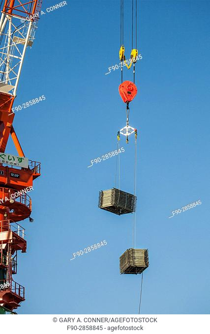 Crane with pulley hook and load at construction site in Kamata, Tokyo, Japan
