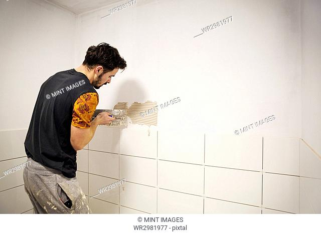 A builder, tiler placing white ceramic tiles on a wall in a bathroom