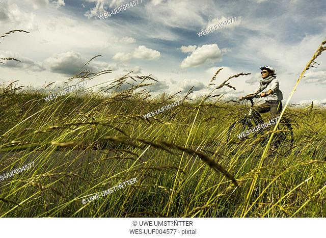 Woman riding bicycle along Moselle