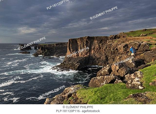 Landscape photographer taking pictures of sea cliffs at Eshaness / Esha Ness during approaching storm in Northmavine, Mainland, Shetland, Scotland, UK