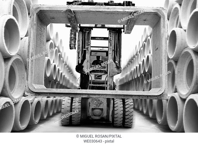 A touring machine in a store aisle, carrying pipes and concrete blocks for construction