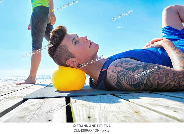 Tattooed man lying on pier using ball as pillow