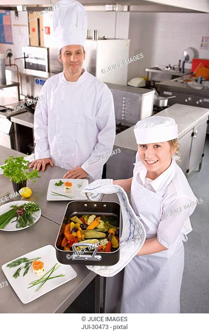 Chef watching trainee holding vegetables in pan in commercial kitchen