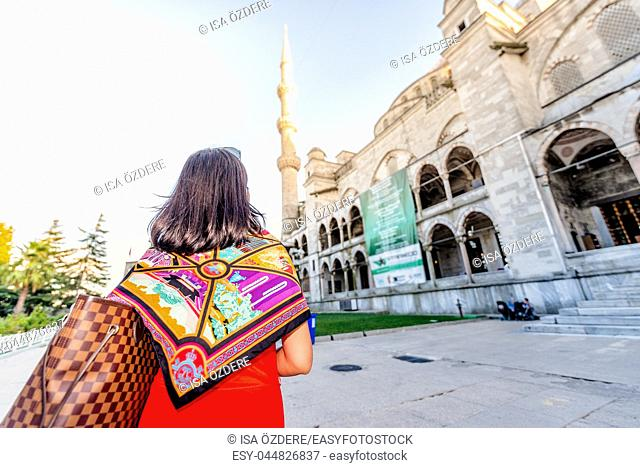 Beautiful woman poses with view of Sultanahmet or Blue Mosque on background in Istanbul,Turkey