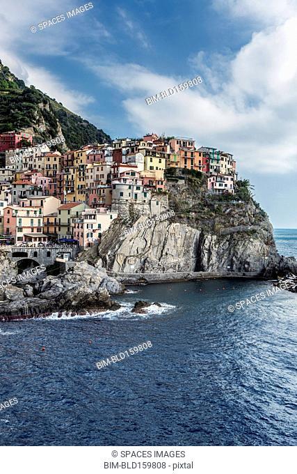Buildings on rocky Manarola coastline and ocean, La Spezia, Italy
